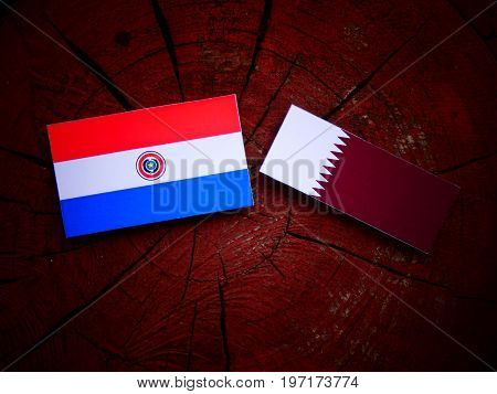 Paraguay Flag With Qatari Flag On A Tree Stump Isolated