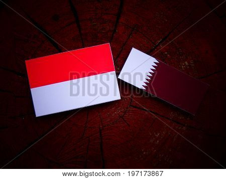 Indonesian Flag With Qatari Flag On A Tree Stump Isolated