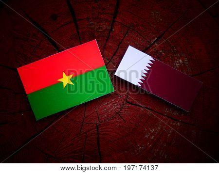 Burkina Faso Flag With Qatari Flag On A Tree Stump Isolated