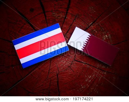 Costa Rican Flag With Qatari Flag On A Tree Stump Isolated