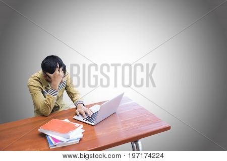 Stressed Man With Head In Hands On Wooden Desk With Tablet.