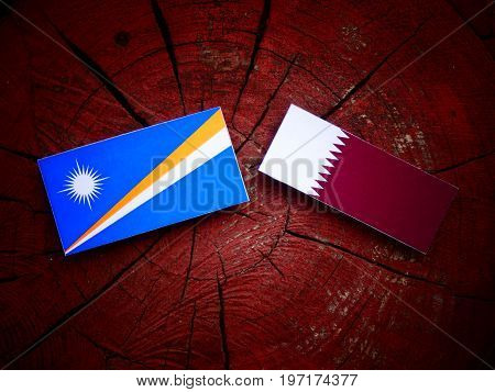 Marshall Islands Flag With Qatari Flag On A Tree Stump Isolated