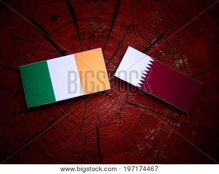Irish Flag With Qatari Flag On A Tree Stump Isolated