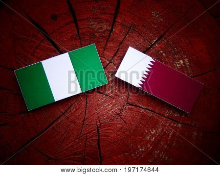 Nigerian Flag With Qatari Flag On A Tree Stump Isolated
