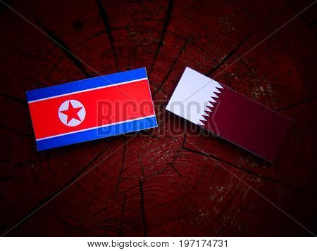 North Korean Flag With Qatari Flag On A Tree Stump Isolated
