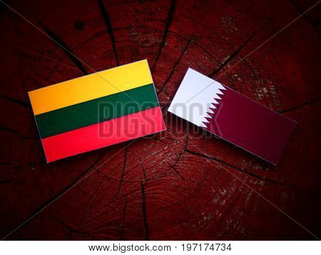 Lithuanian Flag With Qatari Flag On A Tree Stump Isolated