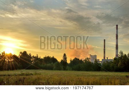 Red and white industrial chimneys. Factory chimneys producing electricity.