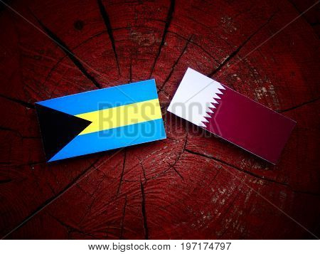 Bahamas Flag With Qatari Flag On A Tree Stump Isolated
