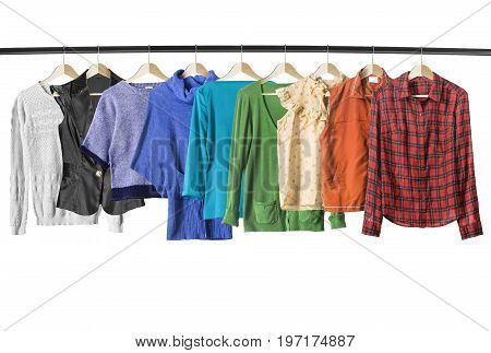 Set of colorful shirts and pullovers on clothes racks isolated over white