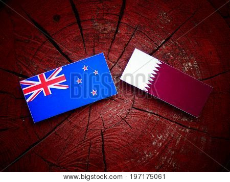 New Zealand Flag With Qatari Flag On A Tree Stump Isolated