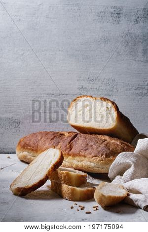 Homemade white wheat bread whole and slice served with flour and wheat grain seeds, white linen towel over gray texture kitchen table.