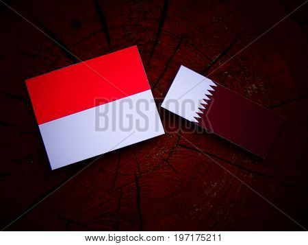 Monaco Flag With Qatari Flag On A Tree Stump Isolated