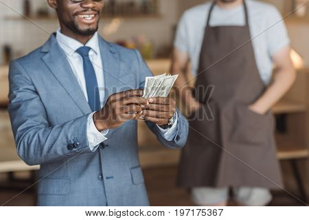 cropped view of handsome african american businessman holding and counting money waiter standing behind in cafe