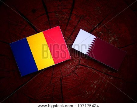 Romanian Flag With Qatari Flag On A Tree Stump Isolated