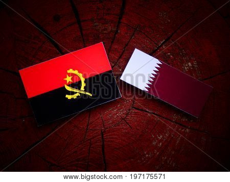 Angolan Flag With Qatari Flag On A Tree Stump Isolated