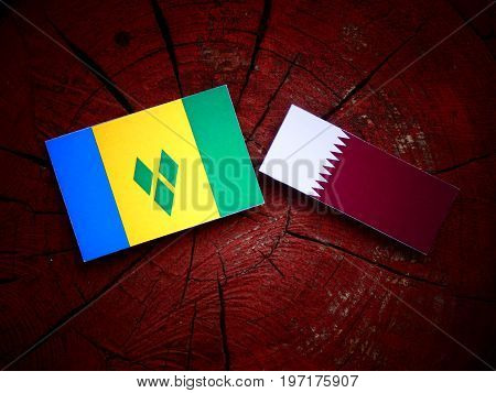 Saint Vincent And The Grenadines Flag With Qatari Flag On A Tree Stump Isolated