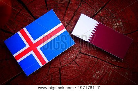 Icelandic Flag With Qatari Flag On A Tree Stump Isolated