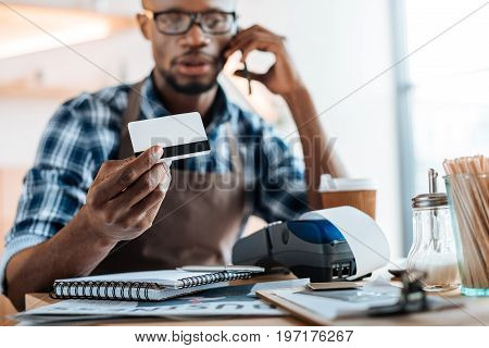 African American Male Owner Working With Credit Card Reader And Smartphone In Coffee Shop