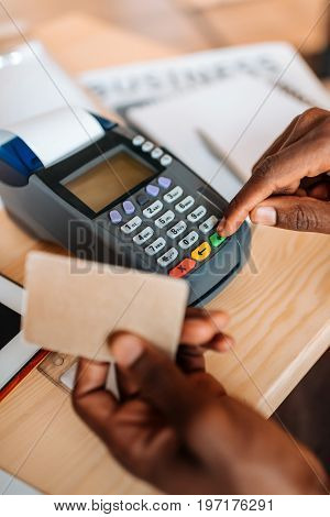 Cropped View Of African American Waiter Working With Credit Card And Terminal In Coffee Shop