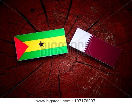 Sao Tome And Principe Flag With Qatari Flag On A Tree Stump Isolated