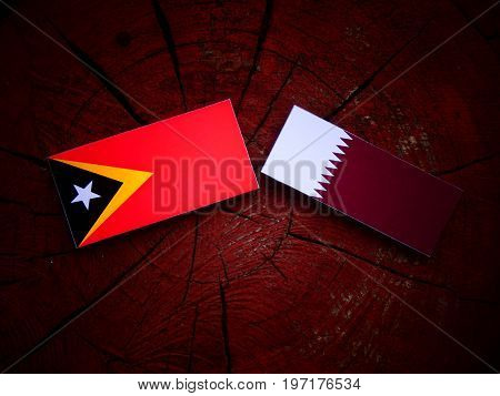 East Timorese Flag With Qatari Flag On A Tree Stump Isolated