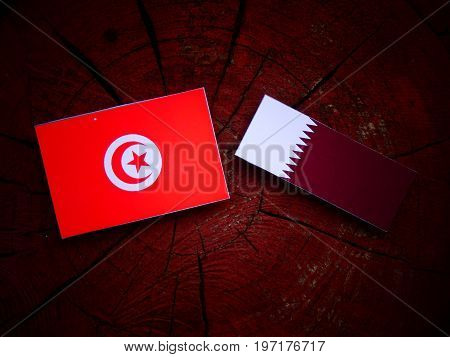 Tunisian Flag With Qatari Flag On A Tree Stump Isolated