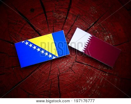 Bosnia And Herzegovina Flag With Qatari Flag On A Tree Stump Isolated
