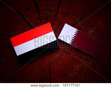 Yemeni Flag With Qatari Flag On A Tree Stump Isolated