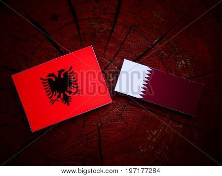 Albanian Flag With Qatari Flag On A Tree Stump Isolated