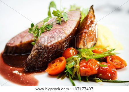 Glazed duck fillet, mashed potatoes seasoned with truffle oil, fig and aniseed sauce