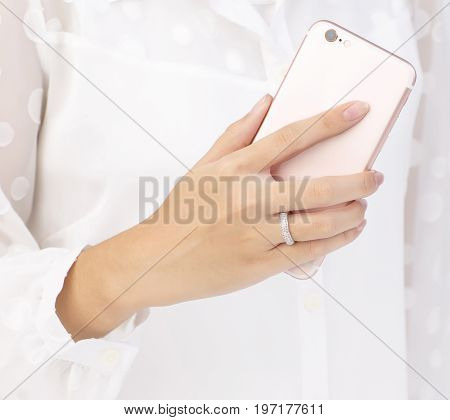 woman's hand with diamond ring holding cellphone showing the backside