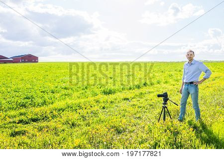 Young Man With Tripod Standing In Vast, Open Summer Countryside Field By Red Building