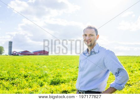 Young Man Standing In Vast, Open Summer Countryside Field By Red Building