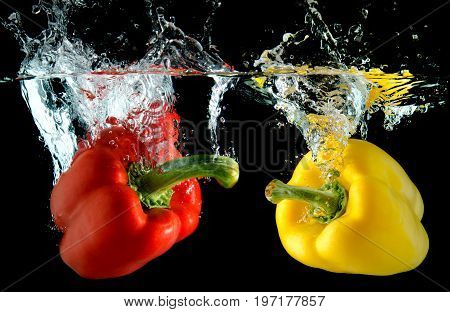 Splash water from water droping bell pepper in black background with studio lighting.