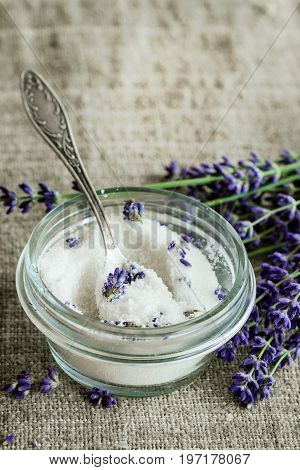 White sugar in glass jars flavored with lavender flowers, standing with tea spoon on table with sackcloth. Rustic style, day light