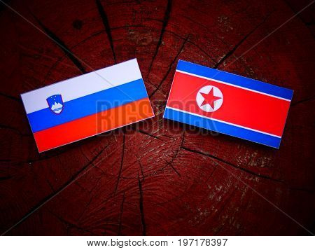 Slovenian Flag With North Korean Flag On A Tree Stump Isolated