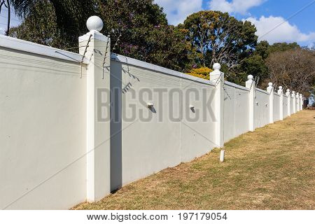 Boundary eight foot high wall with electrified fence for security.