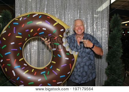 A man holds a Giant inflatable chocolate donut, points and smiles while in a photo booth with a silver sequin background.