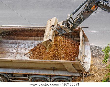 Excavator loading ballast in a gravel truck