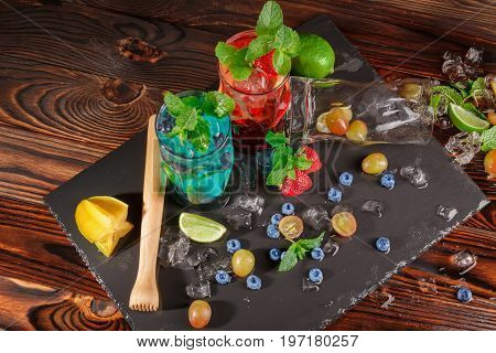 Top view picture of blue and red beverages on a wooden background. Refreshing bright cocktails with mint, lime segments, grapes, bilberries, strawberries, ice and carambola in transparent highball glasses.