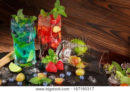 Refreshing blue and red beverages on a black table-napkin. Colourful cocktails with mint, lime segments, grapes, strawberries, ice in transparent highball glasses on the wooden background.