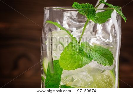 Close-up of a tasty organic beverage with fresh slices of lime, ice and leaves of mint on a wooden background. Summer refreshing beverages for parties.