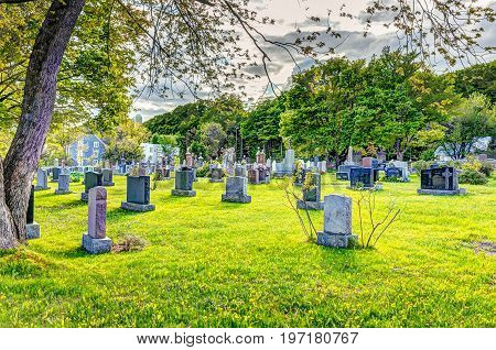 Ile D'Orleans Canada - June 1 2017: Saint-Jean church cemetery with stone gravestones and blue sky in summer