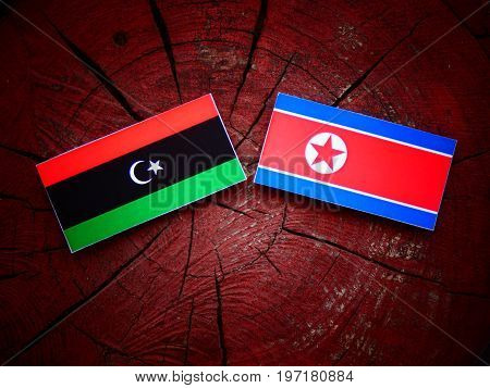 Libyan Flag With North Korean Flag On A Tree Stump Isolated