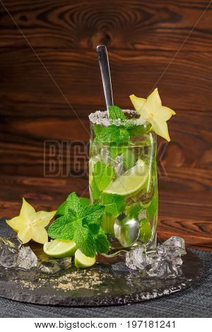 Tasty summer beverage with fresh slices of lime, carambola, ice cubes and leaves of mint in a transparent highball glass with a long tea-spoon on a wooden background.