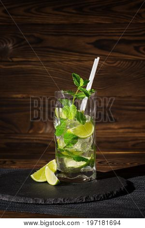 Close-up of a tasty organic beverage with fresh slices of lime, straws, ice and leaves of mint on a wooden background. Summer beverages.