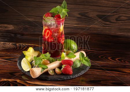 Close-up of a colourful organic beverage with fresh slices of strawberry and lime segments, ice, carambola and leaves of peppermint isolated on a wooden background. Strawberry cocktail in a highball glass.