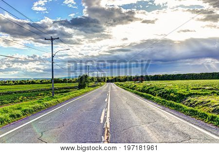 Landscape View Of Chemin Royal Road In Ile D'orleans, Quebec, Canada During Sunset With Sun Rays And