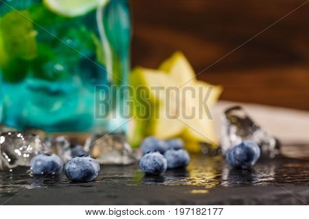 Close-up picture of a blue summer beverage on wooden background. Refreshing bright blue lagoon cocktail with mint, bilberries, ice and carambola in transparent glass. Summer beverages.