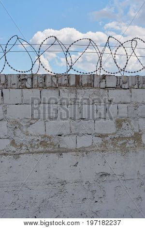 white brick wall with razor barbed wire with blue sky and clouds behind the wall on background. freedom concept